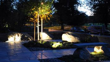 Landscape lighting with rocks, walkway, and trees
